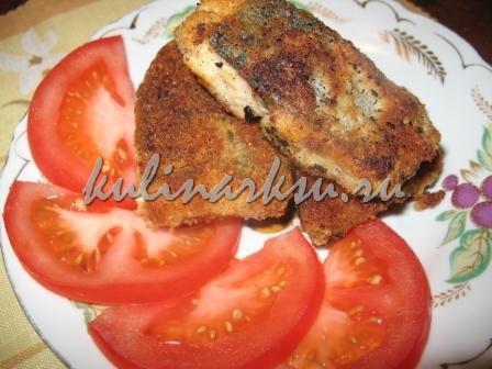 Рыба в сухарях на тарелке с помидорами