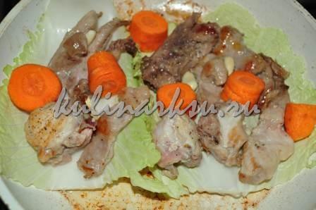 Кролик, морковка и чеснок в кастрюле на листе салата